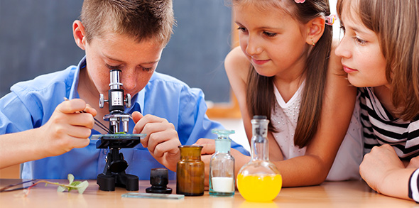 Children performing science experiments in classroom