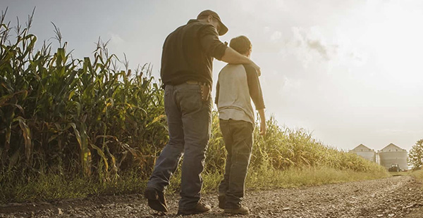 grower and son walking down a dirt path in a corn field