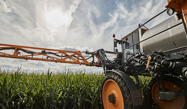 sprayer applying insecticides to a crop field