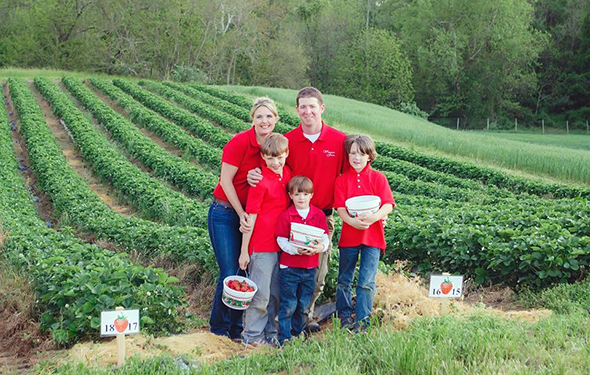 Tyler Wegmeyer and family in front of their strawberry field